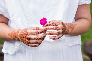 Woman in white dress with henna tattoo on hands holding flowerの写真素材 [FYI03618914]