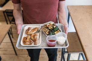 Customer with tray of grilled chicken, vegetables and dipping sauce in restaurantの写真素材 [FYI03619184]
