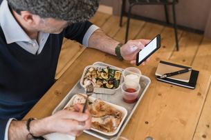 Businessman using smartphone and eating grilled chicken in restaurantの写真素材 [FYI03619187]