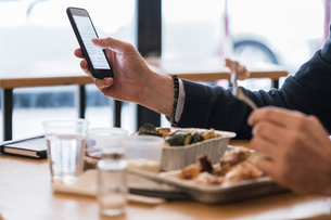 Businessman using smartphone and eating grilled chicken in restaurantの写真素材 [FYI03619189]