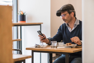 Businessman using smartphone at lunch in restaurantの写真素材 [FYI03619190]