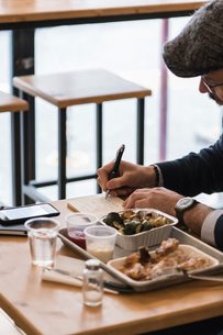 Businessman writing notes over lunch of grilled chicken and vegetables in restaurantの写真素材 [FYI03619191]