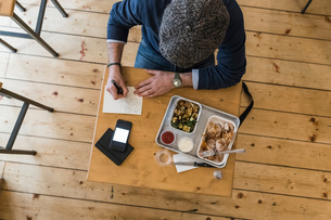 Businessman writing notes over lunch of grilled chicken and vegetables in restaurantの写真素材 [FYI03619192]