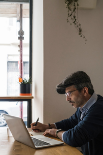Businessman using laptop and writing notes in restaurantの写真素材 [FYI03619194]