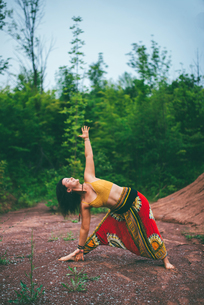 Woman doing triangle pose in forestの写真素材 [FYI03619351]