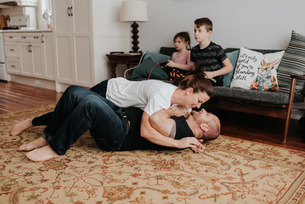 Children playing video game, parents wrestling at homeの写真素材 [FYI03619374]