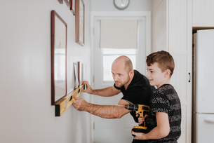 Father teaching son drill wall for picture framesの写真素材 [FYI03619407]