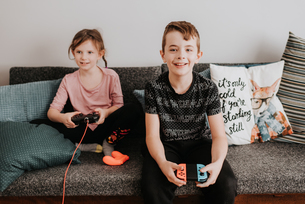 Children playing video game on couchの写真素材 [FYI03619441]