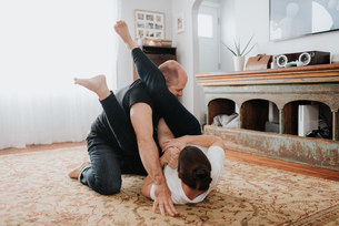 Couple wrestling on carpet at homeの写真素材 [FYI03619444]