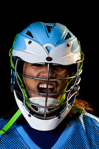 Young male lacrosse player in lacrosse helmet shouting, close up portrait against black backgroundの写真素材 [FYI03619545]
