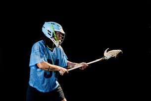 Young male lacrosse player poised with lacrosse stick, against black backgroundの写真素材 [FYI03619547]