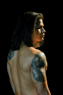 Portrait of young man with tattoo on arm, black backgroundの写真素材 [FYI03619597]