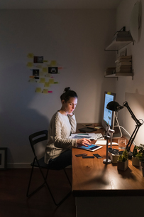Woman working late at homeの写真素材 [FYI03619669]
