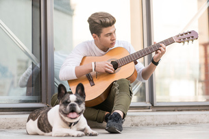 Teenage refugee boy playing guitar on pavement with dogの写真素材 [FYI03619776]