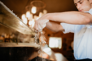 Chef sprinkling flour on pizza dough in open kitchenの写真素材 [FYI03619809]