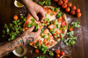 Chef garnishing pizza with basil leaves on kitchen worktopの写真素材 [FYI03619811]