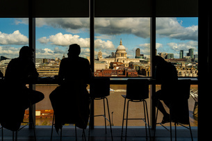 Silhouette of people having conversation by glass window, St Paul's Cathedral in background, City ofの写真素材 [FYI03619817]
