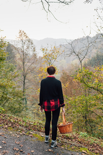 Woman with basket on hillside road, Rezzago, Lombardy, Italyの写真素材 [FYI03619858]