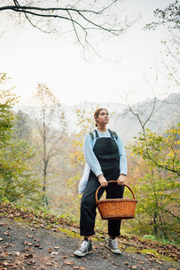 Woman with basket on hillside road, Rezzago, Lombardy, Italyの写真素材 [FYI03619862]
