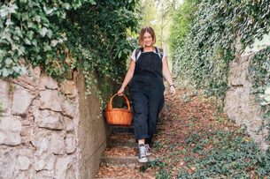 Woman with basket descending ivy-covered stairsの写真素材 [FYI03619903]