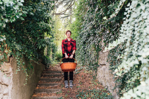 Woman with basket descending ivy-covered stairsの写真素材 [FYI03619905]