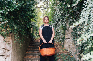 Woman with basket descending ivy-covered stairsの写真素材 [FYI03619907]