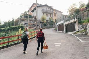 Friends on hillside road, Rezzago, Lombardy, Italyの写真素材 [FYI03619911]