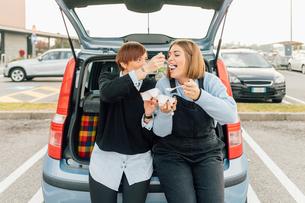 Best friends having takeaway in carpark, Rezzago, Lombardy, Italyの写真素材 [FYI03619921]