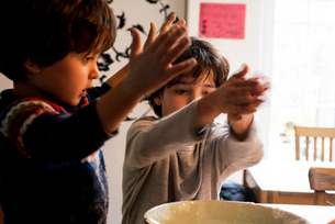 Boys playing with flour in mixing bowlの写真素材 [FYI03619993]