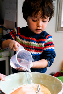 Toddler pouring water into flour in mixing bowlの写真素材 [FYI03619996]