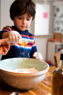 Toddler helping mother pour oil into flour in mixing bowlの写真素材 [FYI03620004]