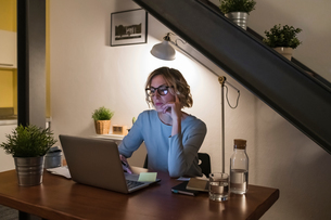 Woman working late at laptop in home officeの写真素材 [FYI03620006]