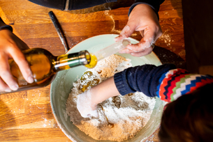 Woman pouring oil into flour in mixing bowlの写真素材 [FYI03620009]