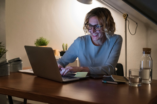 Woman using laptop in home officeの写真素材 [FYI03620011]