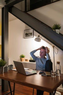 Woman working late at laptop in home officeの写真素材 [FYI03620012]