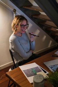 Woman working at laptop and talking on cellphone in home officeの写真素材 [FYI03620014]