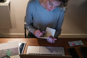 Woman at laptop, writing in notebookの写真素材 [FYI03620015]