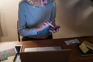 Woman working at laptop and texting in home officeの写真素材 [FYI03620016]