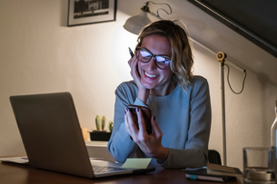 Woman at laptop, smiling at text message on cellphoneの写真素材 [FYI03620018]