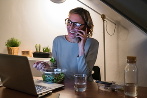 Woman working late at laptop, talking on cellphone and having salad dinnerの写真素材 [FYI03620024]