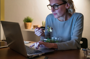 Woman working late at laptop and having salad dinnerの写真素材 [FYI03620025]