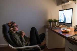 Woman relaxing in front of TV with mug of warm drinkの写真素材 [FYI03620029]