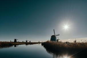 Windmills along canal at dusk, Kinderdijk, Zuid-Holland, Netherlandsの写真素材 [FYI03620033]