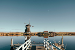 View of windmill along canal from pier, Kinderdijk, Zuid-Holland, Netherlandsの写真素材 [FYI03620034]