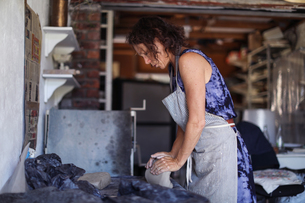 Female potter shaping clay in workshopの写真素材 [FYI03620043]
