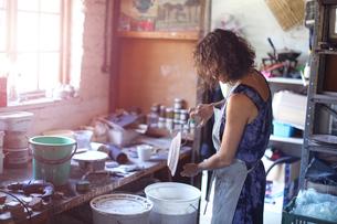 Female potter glazing ceramic in workshopの写真素材 [FYI03620044]