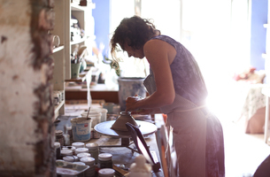 Female potter shaping clay on pottery wheel in workshopの写真素材 [FYI03620045]