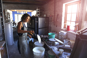 Female potter glazing ceramic in workshopの写真素材 [FYI03620048]