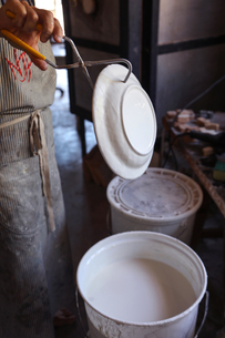 Female potter glazing ceramic in workshopの写真素材 [FYI03620050]