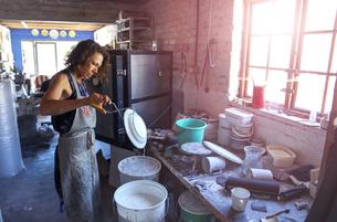 Female potter glazing ceramic in workshopの写真素材 [FYI03620051]